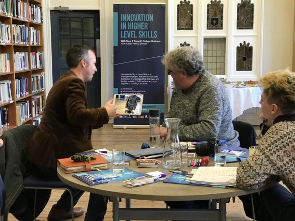 Discussion going on around a round table with three people, two men and a woman. One man is wearing a brown velvet jacket and has short dark brown hair. The other man has grey curly hair and a woolly jumper. The man in the brown jacket is showing the man in the jumper a 3D model using augmented reality on an iPad. The woman is looking on. She is wearing a pattered jumper with rows of diamond, stars and geometric knitting shapes (like a Fair Isle pattern). She short hair, shaven sides and dyed blonde and curly on top. The table is full of notebooks and brochures, glass and bottles of water. Around them is a big bookcase and a banner saying Innovation in Higher Level Skills.