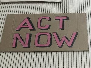 Protest sign from Black Voices Cornwall Black Lives Matter protests in Cornwall. Act Now painted in pink and black on cardboard