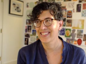 Photograph of Ananda Rutherford smiling and wearing glasses, short curly hair with pictures and photos in the background.