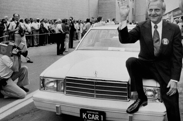 Chrysler Corp. Chairman Lee Iacocca, right, sits on the fender of K Car Number One, a Plymouth Reliant, Wednesday, Aug. 7, 1980, Detroit, Mich. The automaker showed off its new front-wheel drive model. The car will also be sold as the Dodge Aries, and will be manufactured in Detroit and Newark, Delaware. (AP Photo/Dale Atkins)