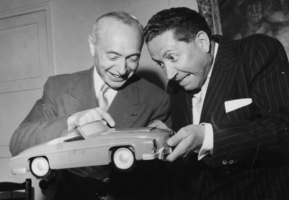 An uncharacteristically jovial J.A. Grégoire (on the left) showing his latest model to singer Jean Rigaux, circa 1956. (Photo by Keystone/Hulton Archive/Getty Images)