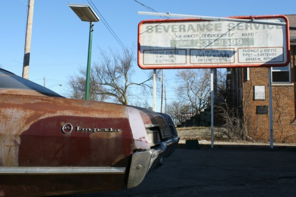 1967 Chevrolet Impala hardtop sedan, with Severance Service sign and brick house in the background.