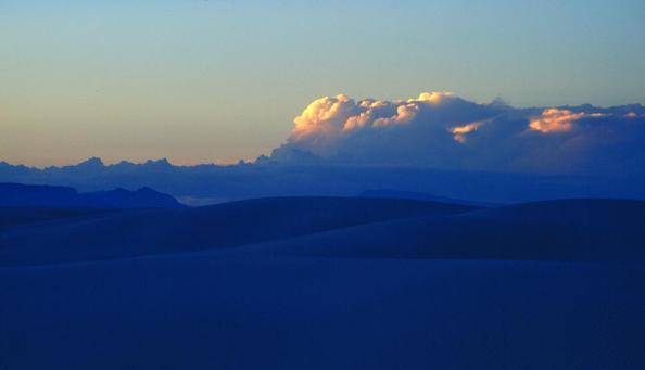 Nuvens onduladas sobre baixas colinas.