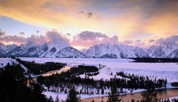 Parque Nacional Grand Teton, Wyoming. Montanhas Grand Tetons e rio Snake com neve e nuvens no céu.
