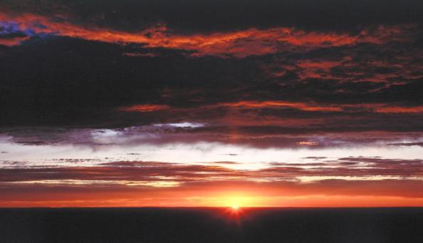 Parque Nacional Grand Canyon, Arizona. Entardecer no horizonte sob nuvens tênues.