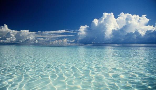 A superfície da água tropical azul-esverdeada sob um céu azul profundo repleto de nuvens brancas.