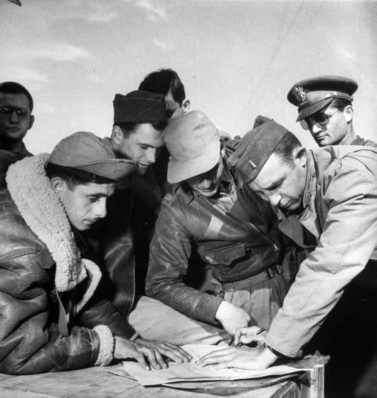 La tripulación de un B-17 y hombres de la inteligencia compartiendo información