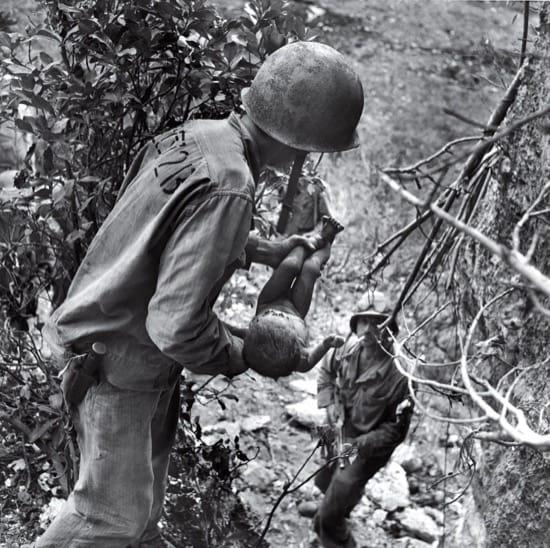 Un marine sostiene un bebé malherido, durante los combates en Saipan. El bebé fue el único ser humano encontrado vivo en una cueva donde había centenares de muertos