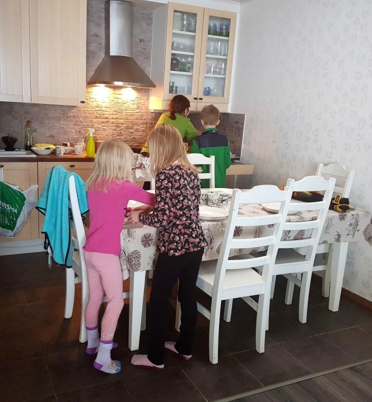 Lunia og Menja dekker bord, mens Johanna lager mat