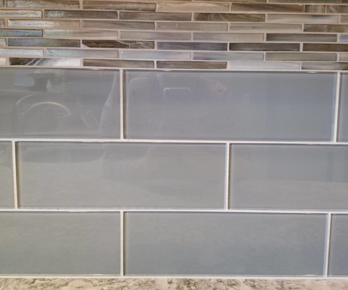 "Glazzio Crystile series glass subway tiles in Gray Sky 4"" x 12"" with a border of Lunada Bay Agate Pisa Pearl 1.2"" x 4"" brick mosaic"