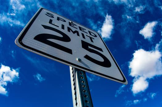 25 Miles Per Hour Speed Limit Sign Set Against Blue Sky