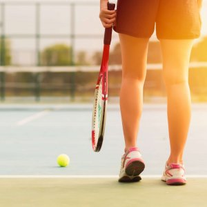 Tennis player holding racket preparing for playing game on outdoor court during summer.