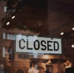 Closed Sign Hanging on a Glass Window Door