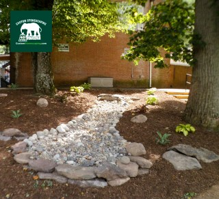 Custom Stonescaping piped out the gutters from the building and directed them to the dry creek bed we built to slowly carry the water down the hill and allow it to percolate into the ground. Custom Stonescaping also added some decorative boulders and plants.