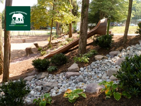 Custom Stonescaping installed two slides into the hillside and installed lots of plants and decorative boulders to create a natural looking play area. Custom Stonescaping also installed dry creek beds for proper drainage.