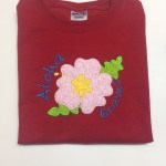 pink hibiscus flower applique on red shirt with aloha and grams personalization