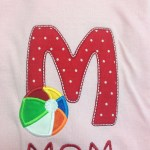 red poka dot applique M with applique beach ball in primary colors