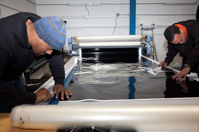 After printing the sections the next step is laminated them. Here, Kwasi Boyd (left) and Sandor Price trim the laminated sections at Custom Vehicle Wraps. Photo by Lori Eanes for the Wall Street Journal.