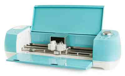 An aqua blue Cricut Explore Air 2 sits with the lid open, showing the cutting heads.