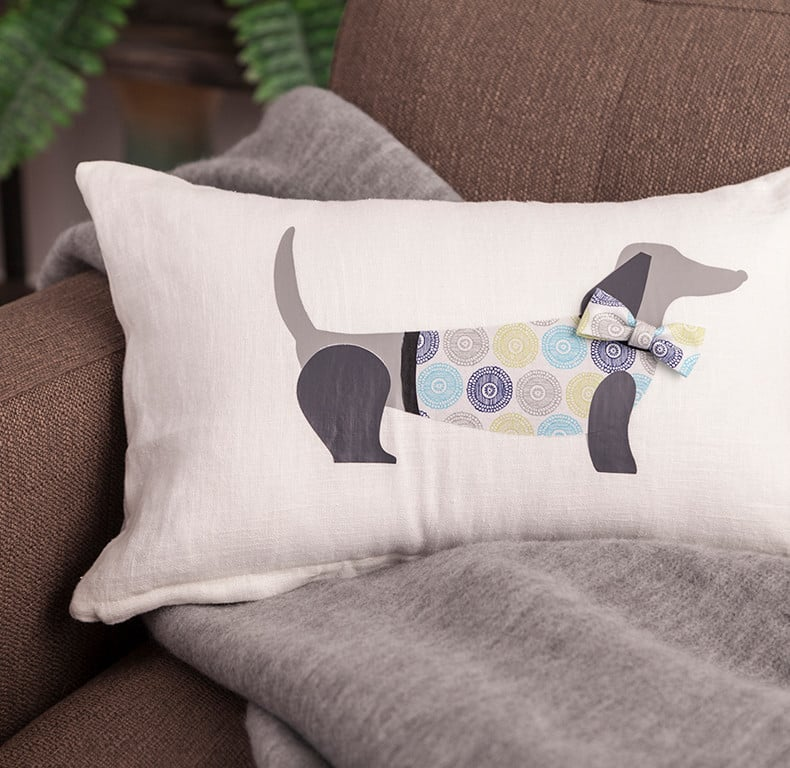 A custom pillow decorated with an iron-on vinyl puppy sits on a couch.