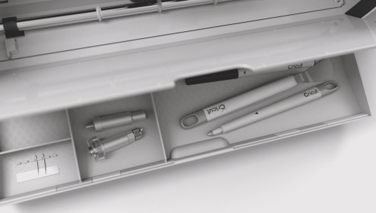 The new and improved storage drawer of the Cricut Maker holding accessories and blades