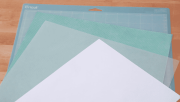 The blue Cricut cutting mat and cutting materials.