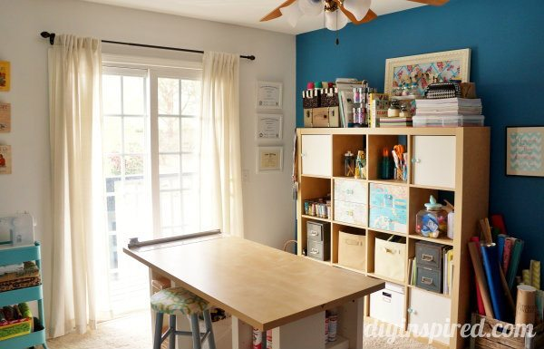 Cubbies under the table and up against a dark teal wall
