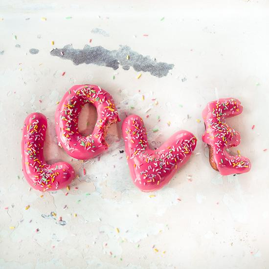 Zum Valentinsttag gibt es Love Donuts mit Zuckerguss und bunten Streuseln