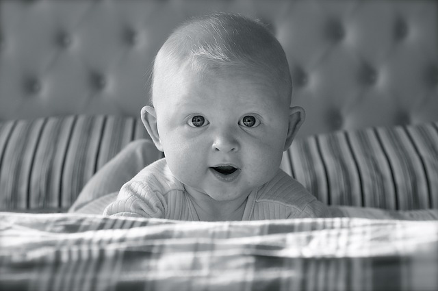 baby looking up from bed