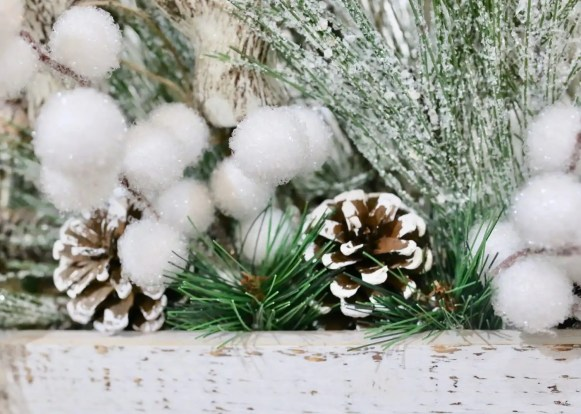 Hot glue pine cones and greenery.