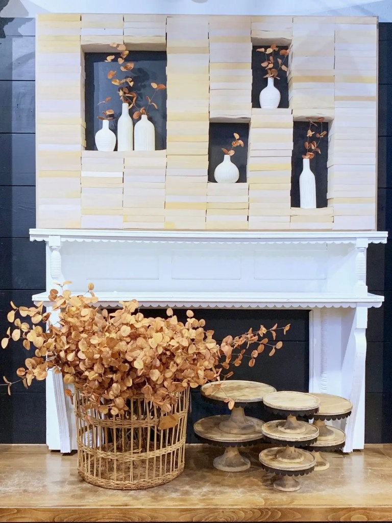 Fall Magnolia Market Display of stacked books encasing vases of fall stems