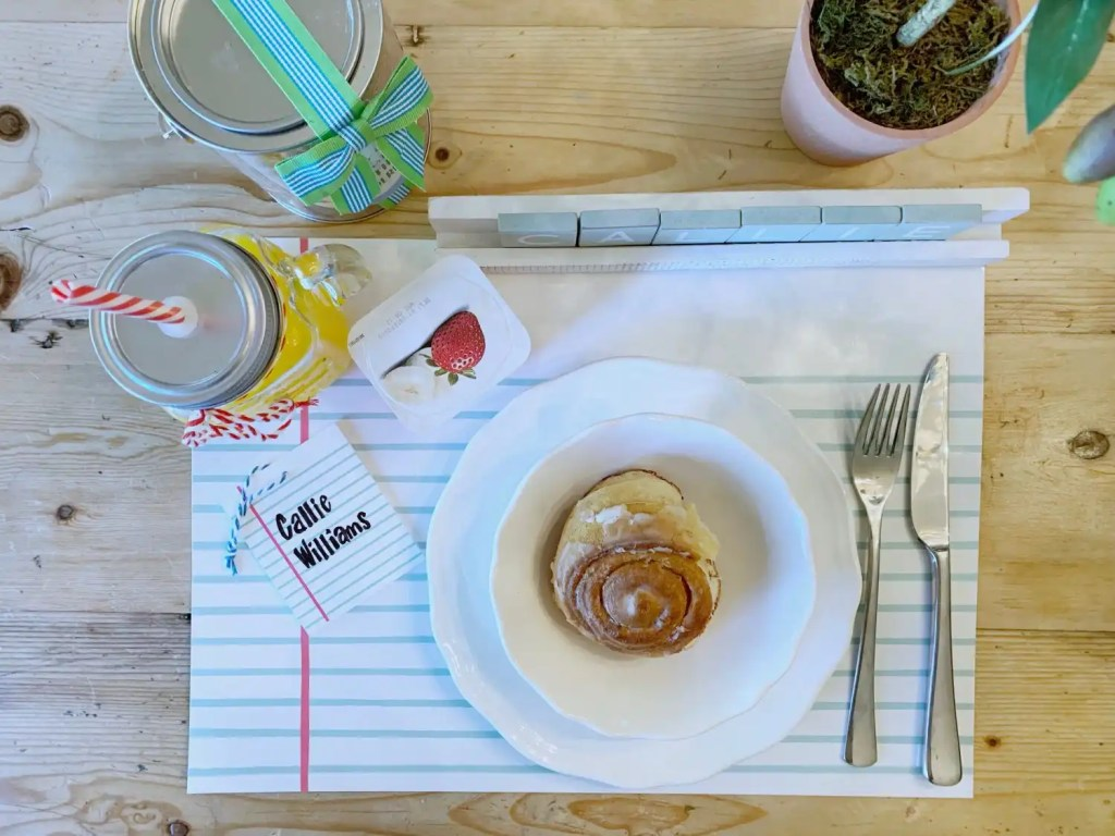 Back to School themed breakfast with cinnamon roll, yogurt and juice on a notebook paper placemat.