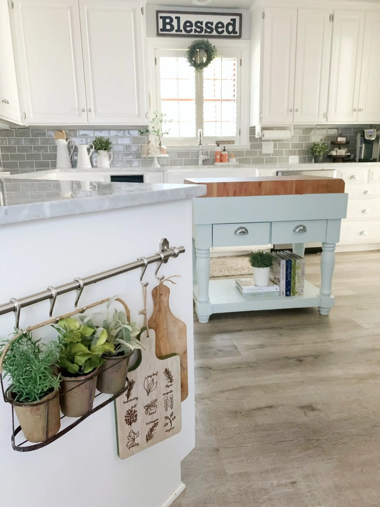 Potted greenery and small cutting boards hung from decorative hooks on kitchen island.