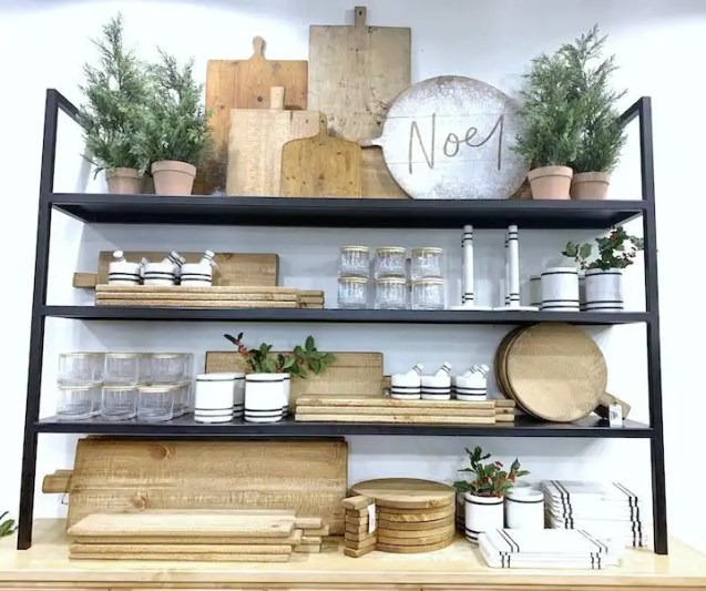 Shelf styling using cutting boards, pine trees, marble accessories in Magnolia Market Waco.