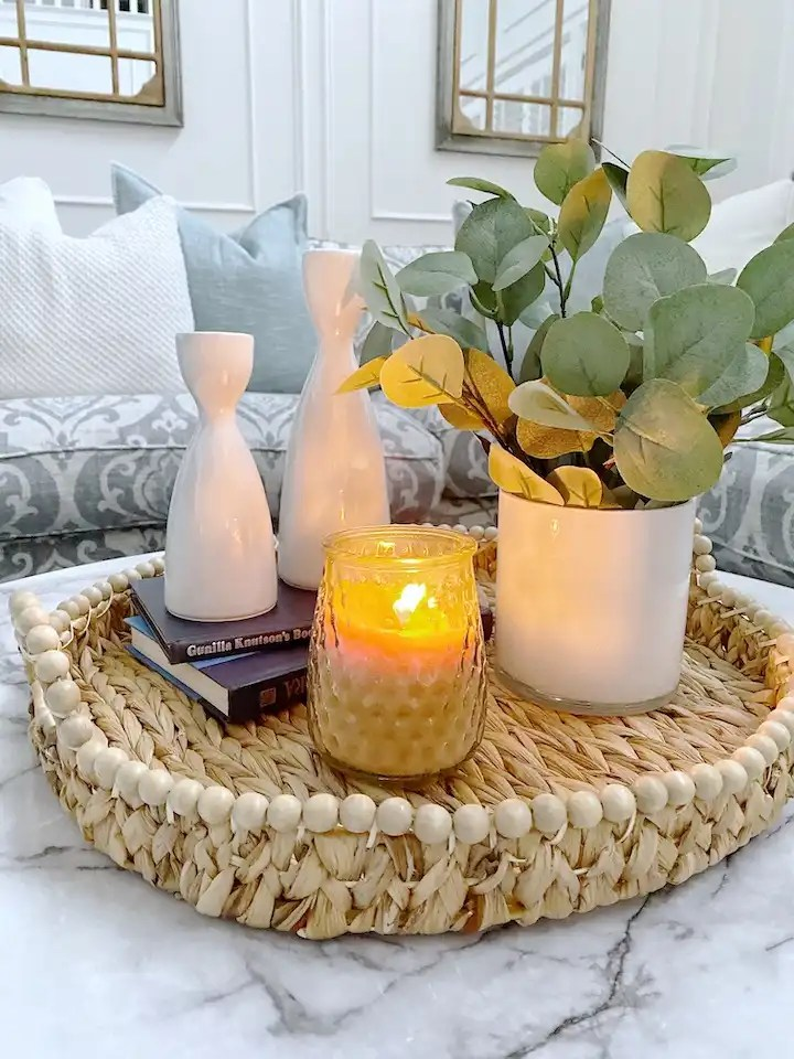tray decorated with candle, plant, books, candlesticks on coffee table