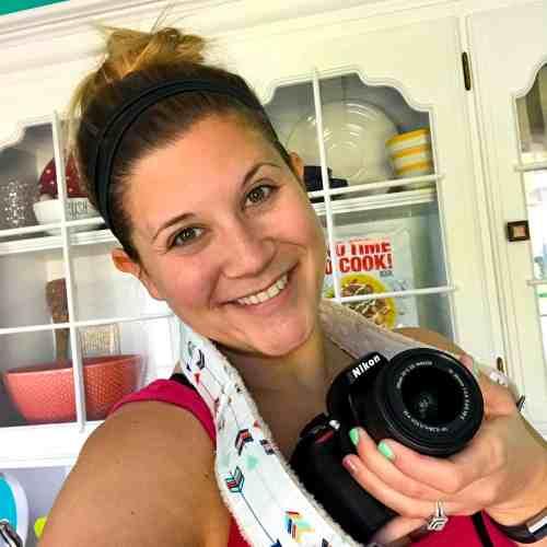Headshot of Caitlin holding Nikon camera