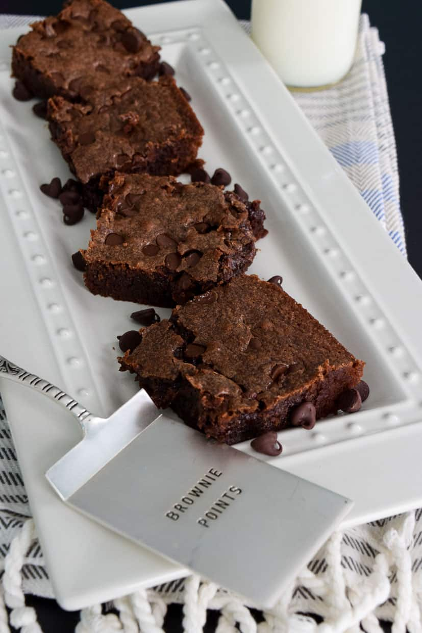 """Chocolate Chip Brownies on white platter with """"brownie points"""" spatula in front"""