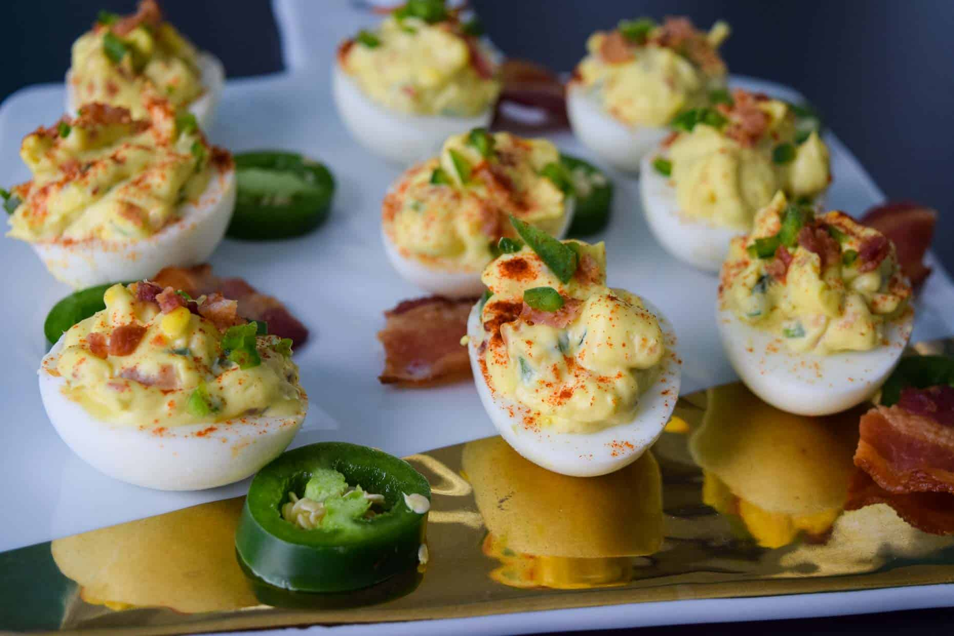 Jalapeno Bacon Deviled Eggs on white and gold platter side view