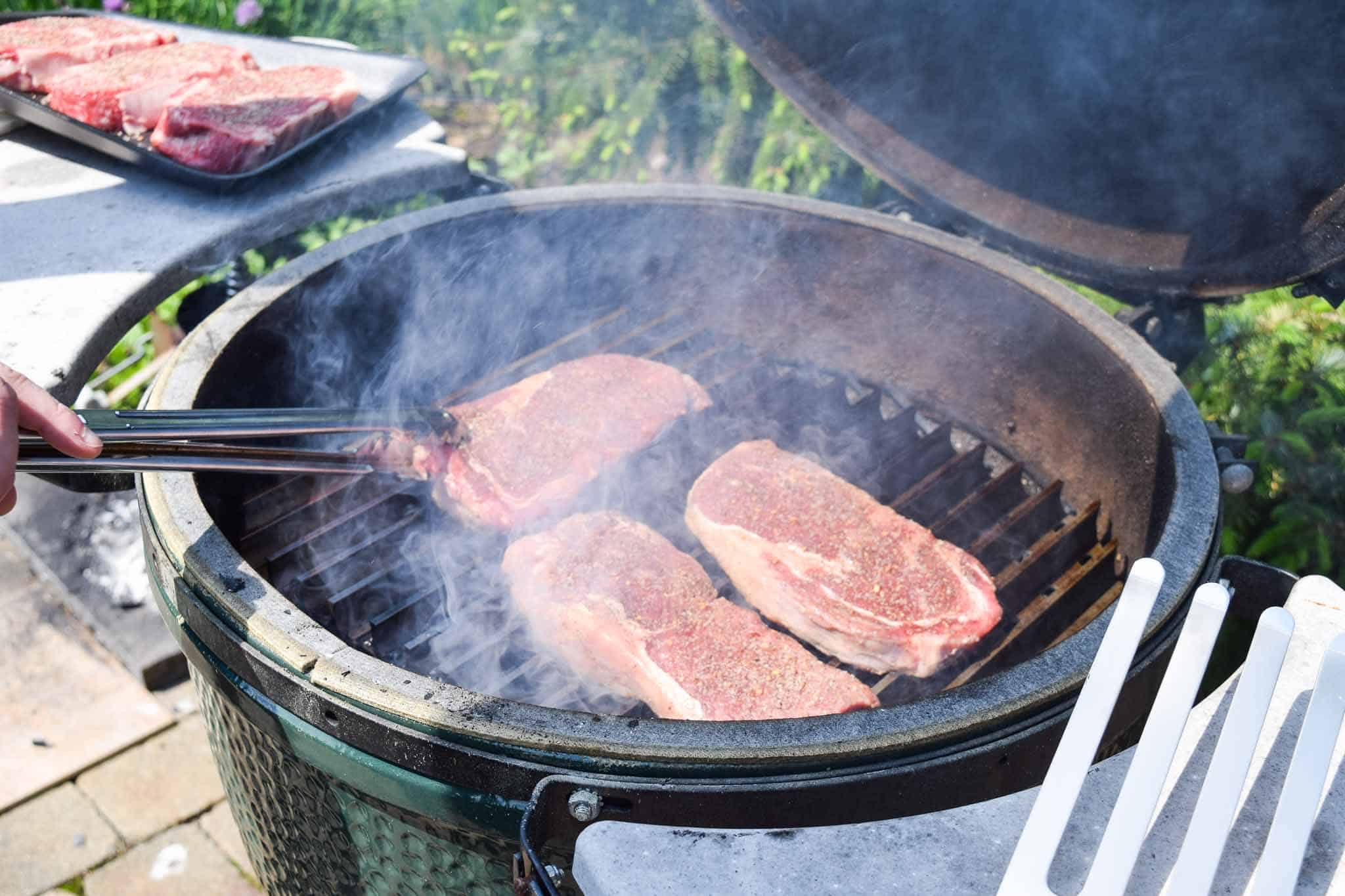 Steaks being flipped with spatula on big green egg grill