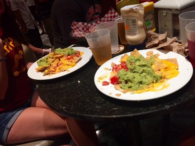 Plates of half eaten nachos on bar table