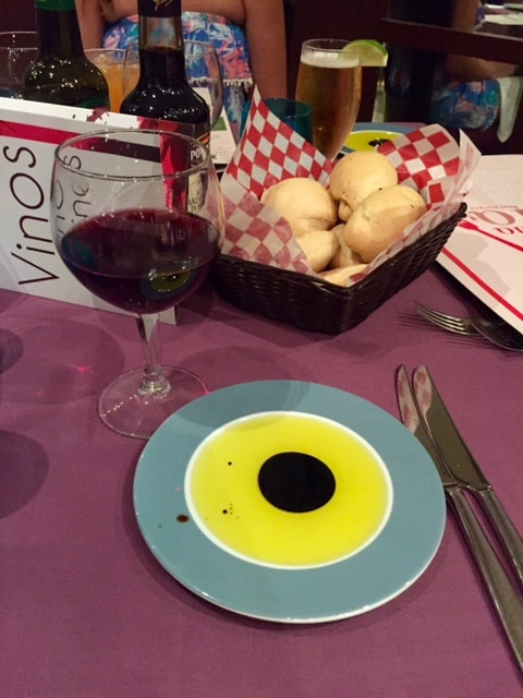 Oil and vinegar on plate beside glass of red wine and rolls