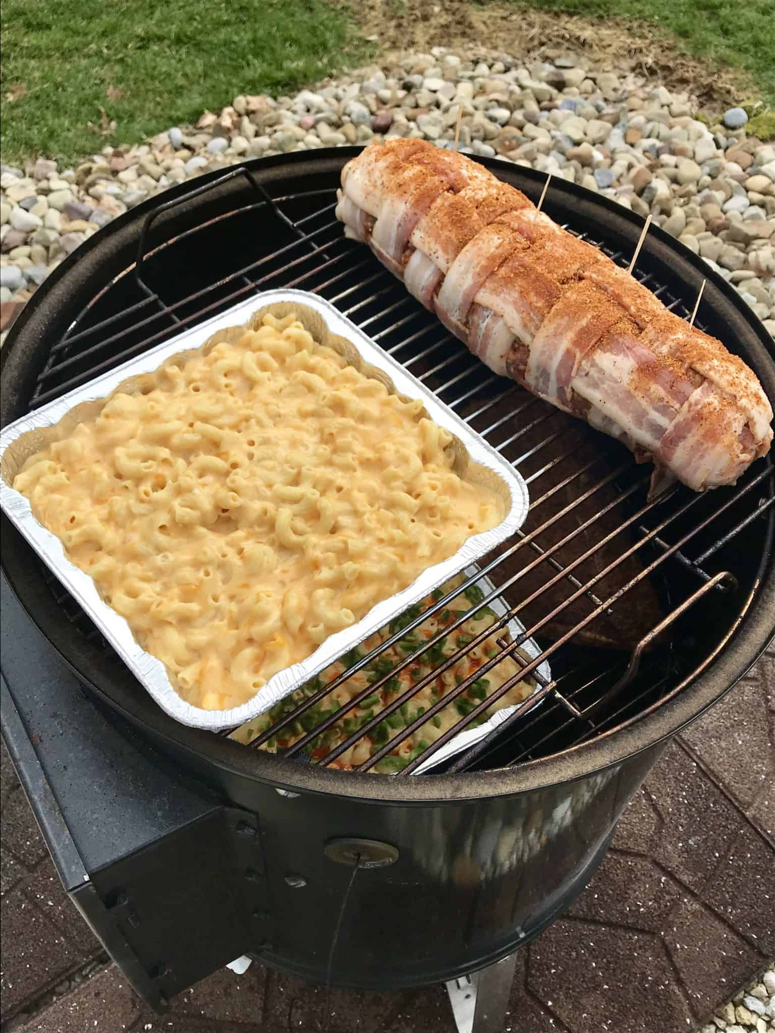 Bacon explosion on weber grill next to pan of smoked Mac and cheese