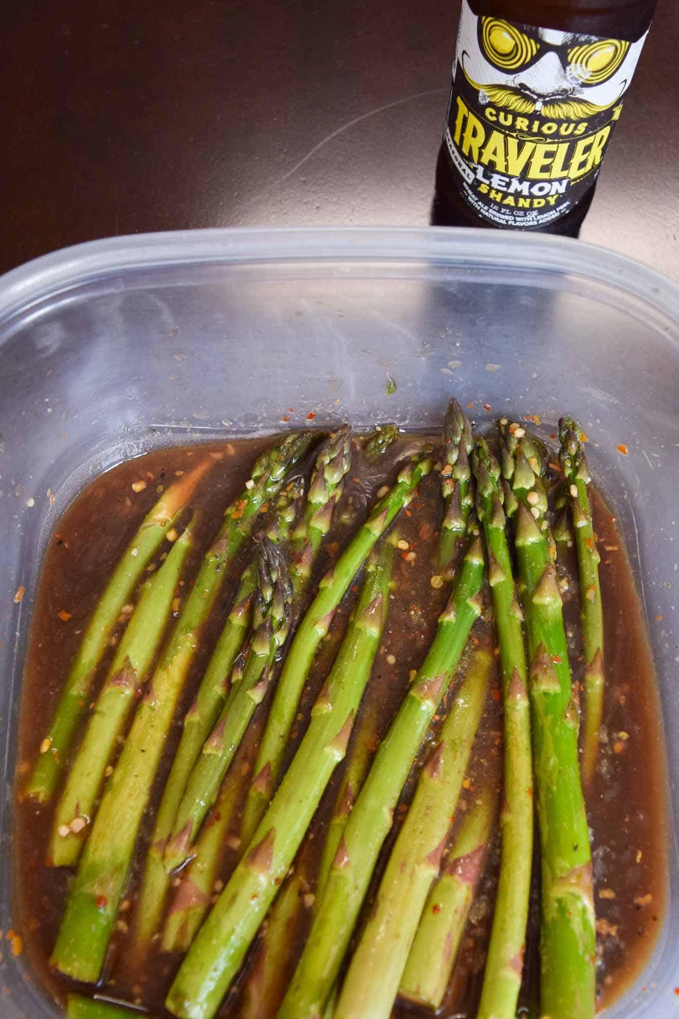 Asparagus marinating in Tupperware container
