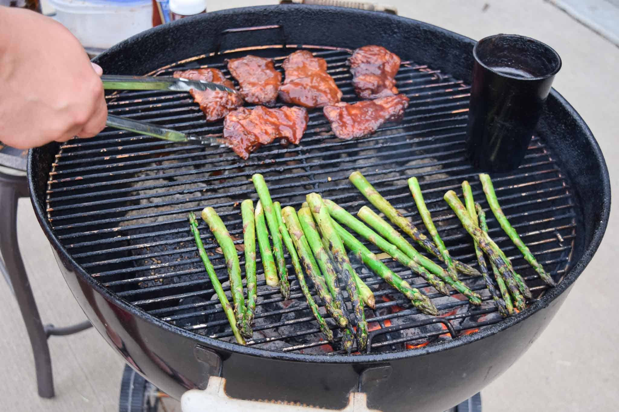 chicken thighs and asparagus on weber grill side view