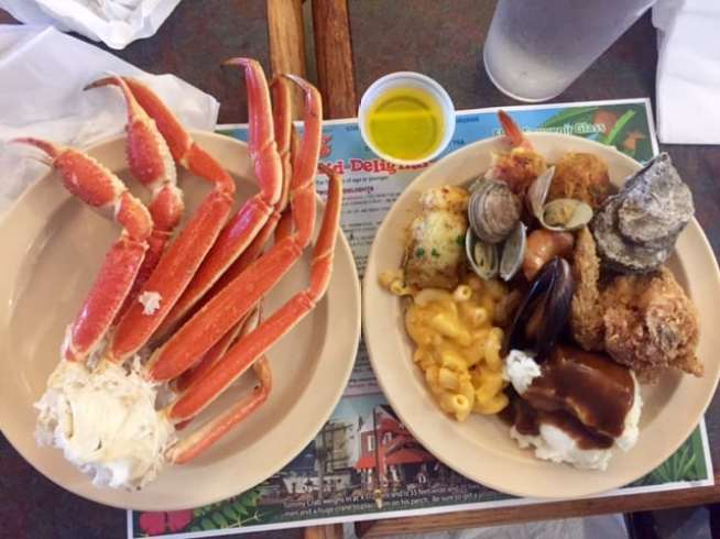 Plate of crab legs beside plate of various side dishes overhead shot