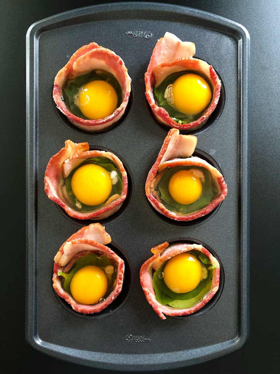 Overhead shot of bacon in small muffin pan with spinach and cracked eggs