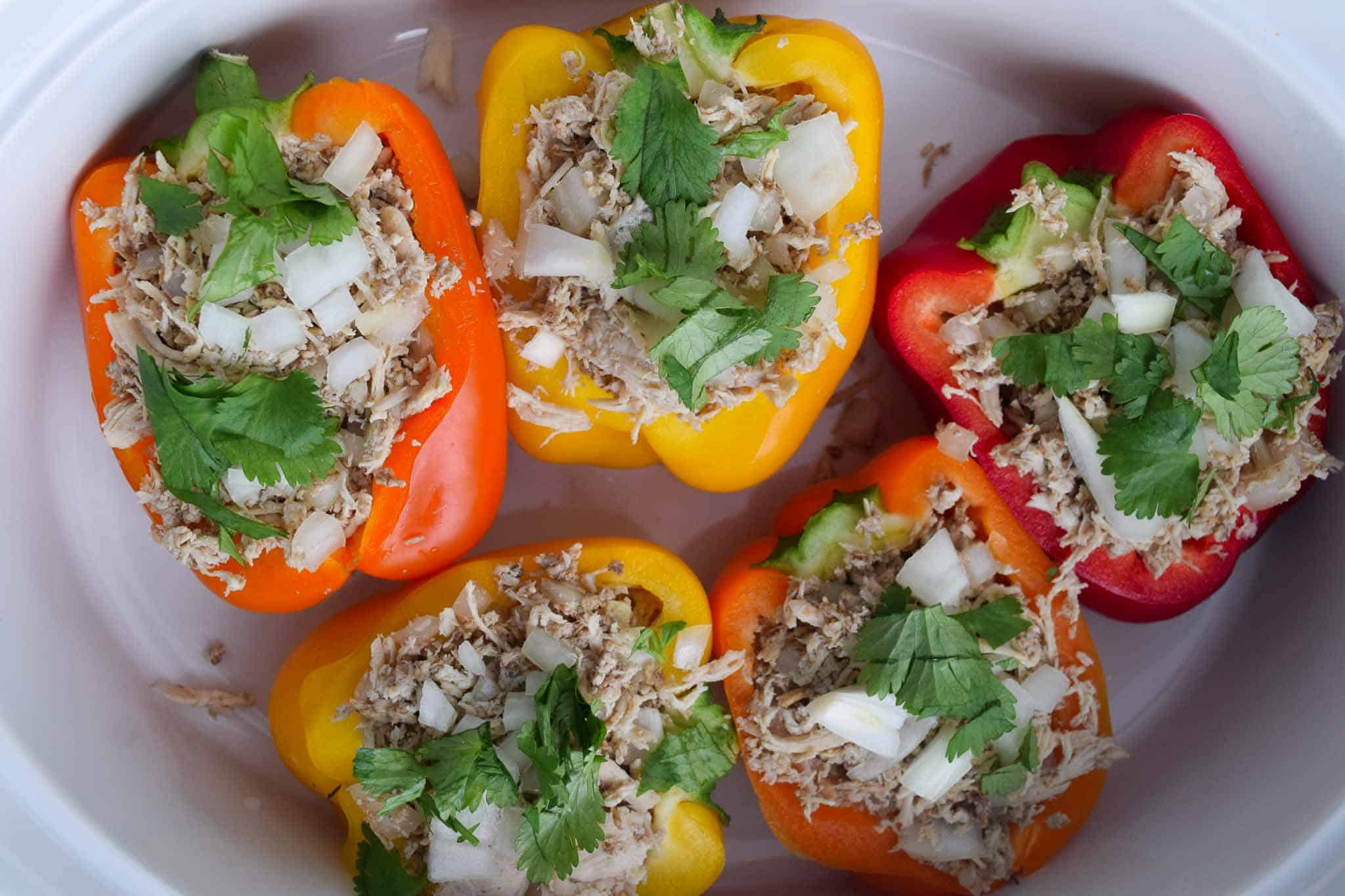 chicken stuffed peppers in white dish topped with cilantro overhead shot