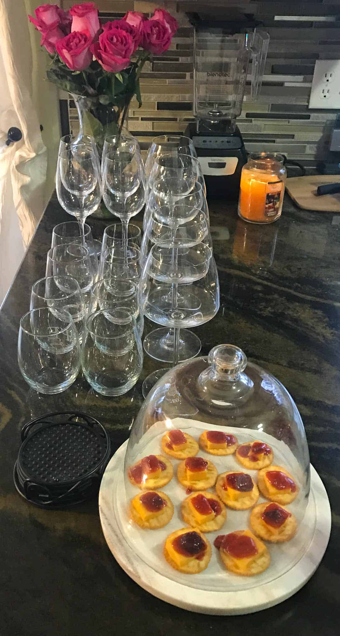 appetizer on globe platter with wine glasses lined up behind it and candle burning in background