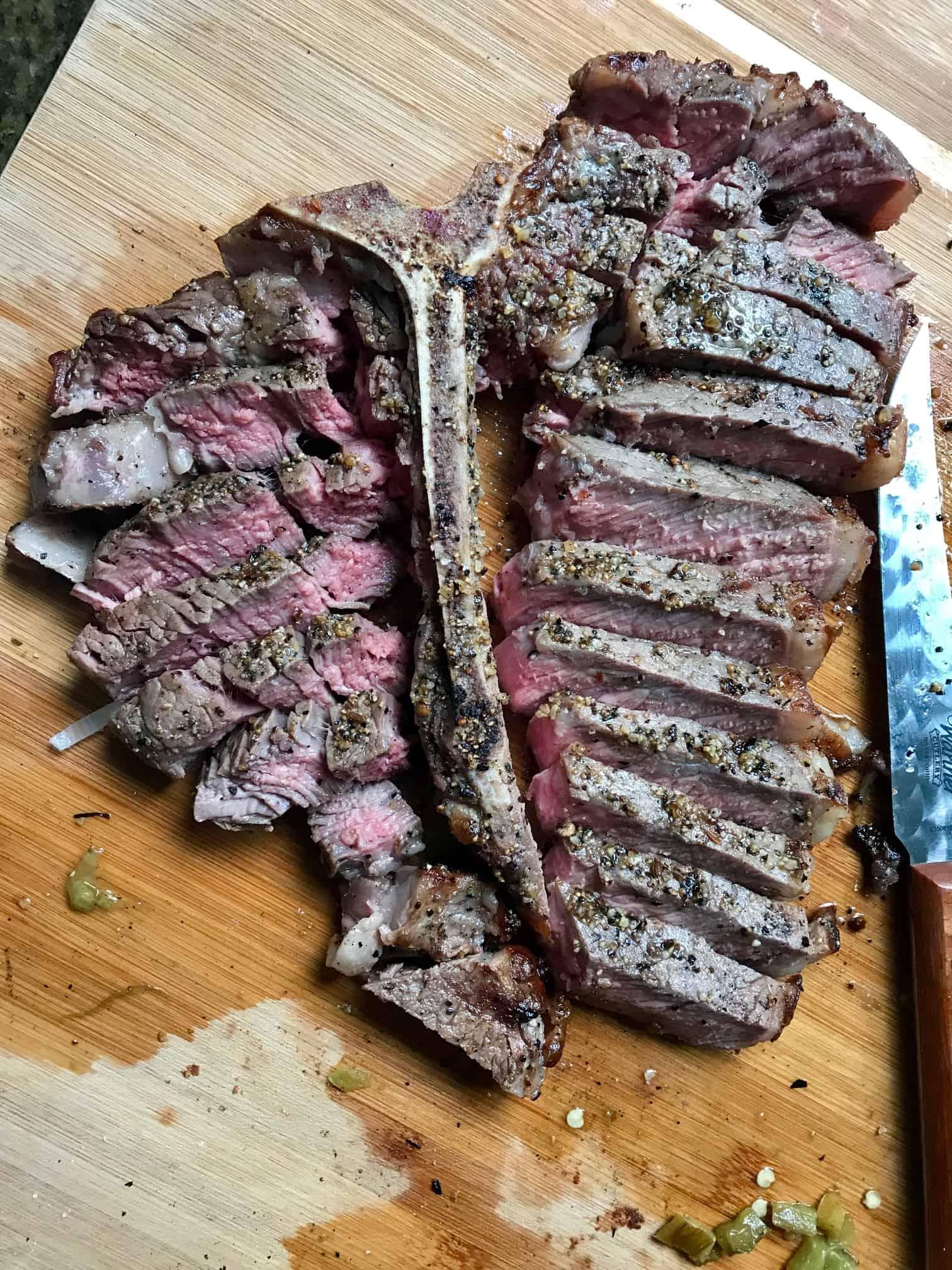 Reverse Sear Steak slices by bone on wooden cutting board