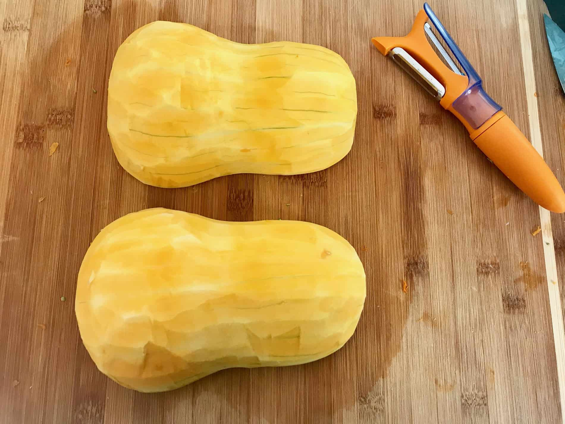 Butternut squash on cutting board cut in half with skin removed